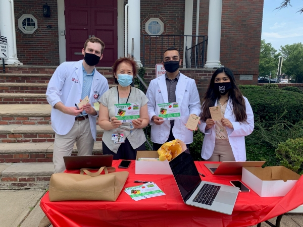 3 medical students and 1 faculty advisor standing in front of building